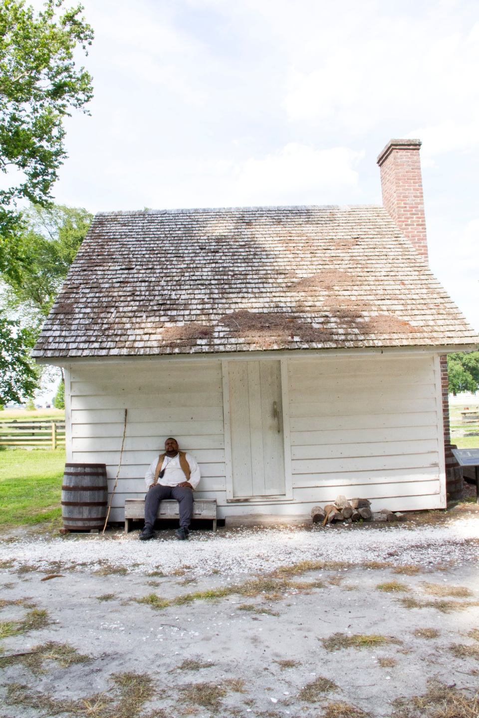 Sitting in front of a enslaved person's reconstructed cabin at Somerset Place